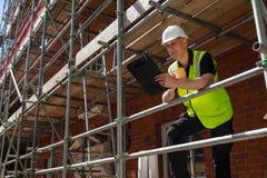 Contramestre Builder da construção na prancheta e na caneca do terreno de construção imagens de stock