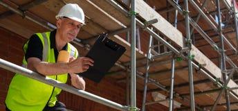Contramestre Builder da construção na prancheta e na caneca do terreno de construção imagens de stock royalty free