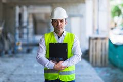 Contramestre no uniforme de trabalho que expertising a estrutura que está com o dobrador no canteiro de obras imagem de stock royalty free