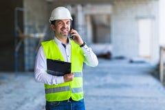 Contramestre no uniforme de trabalho que expertising a estrutura que está com o dobrador no canteiro de obras imagem de stock