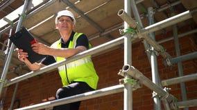 Contramestre, trabalhador ou arquiteto masculino do construtor trabalhando na posição do terreno de construção da construção no a video estoque