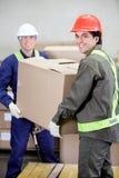 Contramestres que levantam a caixa de cartão no armazém fotografia de stock royalty free