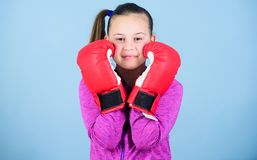 Contrary to stereotype. Boxer child in boxing gloves. Female boxer. Sport upbringing. Boxing provide strict discipline. Girl cute boxer on blue background royalty free stock images