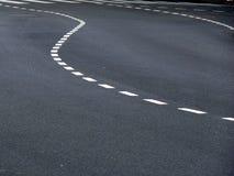 Contrassegni curvi di traffico su asfalto immagini stock