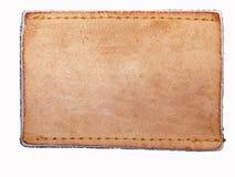 Contrassegno in bianco del cuoio dei jeans sul tessuto del tralicco immagini stock libere da diritti