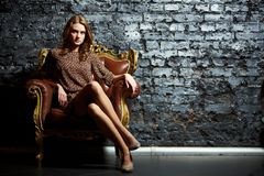 Contrast. Gorgeous girl sitting in a vintage chair presenting the contrast of high fashion and grunge royalty free stock photography
