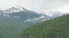 Snow-capped Caucasus mountains 001. Contrast of Caucasus mountains, green forests against snow-capped mountains stock footage