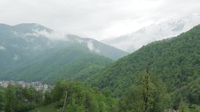 Snow-capped Caucasus mountains 002. Contrast of Caucasus mountains, green forests against snow-capped mountains stock video footage