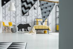 Contrast color child`s bedroom. With yellow chair and black bear sticker on white wall with trees Royalty Free Stock Photography