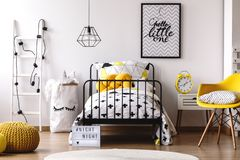 Contrast color kid`s bedroom. Paper bag for toys next to bed in contrast color kid`s bedroom with yellow pouf, chair and clock stock image