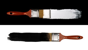 Contrast Concept. Two paint brushes representing contrast: white paint on black background and black paint on white background stock photography