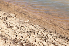 Contrast concept of dry cracked mud next to water Royalty Free Stock Photos
