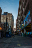 Contrast between creative artistry and waste. Downtown Phoenix side alley with colorful artwork reflecting the morning light on August 11, 2017. Trash dumpsters royalty free stock photos