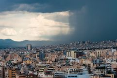 Contrast dark wall of falling water from the moody sky of the coming storm on the city. Panoramic cityscape view on Greece capital. Athens, Greece - June 12 royalty free stock photography