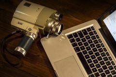 Contrast between different periods of technology: a vintage Super 8 cine camera from the 1960 Minolta Zoom 8 with an actual. Computer laptop stock photography