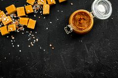 Contrast of flavors. The combination of salty and sweet. Caramel sauce in glass jar near caramel cubes on black Royalty Free Stock Photos
