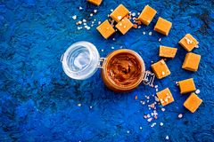 Contrast of flavors. The combination of salty and sweet. Caramel sauce in glass jar near caramel cubes on blue Stock Image