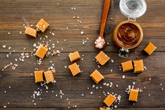 Contrast of flavors. The combination of salty and sweet. Caramel sauce in glass jar near caramel cubes on dark wooden Stock Image