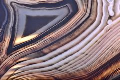 Contrast light and dark brown lines in agate. Background with contrast agate structure royalty free stock photos