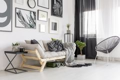Contrast living room interior. Armchair next to wooden sofa in contrast living room interior with gallery of posters royalty free stock photo