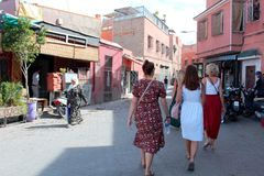 Moroccan woman in traditional djeallabah and tourists in European clothes in a street of Marrakesh stock photo