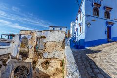 Contrast between new and dilapidated house. A new house and a dilapidated house next to each other in the blue city of Chefchaouen royalty free stock photo
