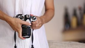 Contrast between old and modern times: a young woman fiddles with her vintage camera hanging from her neck. Contrast between old and modern times: a young woman stock video footage