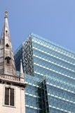 Contrast between old and new and between clerical and profane. Old church and modern office building in London, United Kingdom royalty free stock images