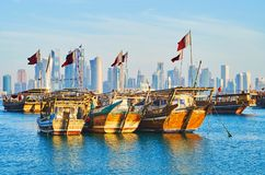 Traditional boats and modern architecture of Doha, Qatar. The contrast of old wooden dhows, moored in harbor and the modern skyscrapers of Al Dafna district on Royalty Free Stock Image