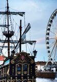 Old sailing ship and a modern Ferris wheel. The contrast between the past and the present-an old sailing ship and a modern Ferris wheel stock photos