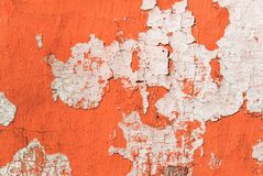 Contrast photograph of an old faded red wall with defects and remnants of fragments of light plaster of an abstract form. Resembling a fancy geographic map royalty free stock image