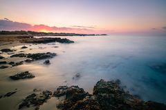 Bipolar. The contrast and strength of the rocks and sand collide with the calm and tranquility of the sea and the pastel colors of the image stock images