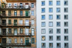 Contrast between the old and new building. A contrast between two houses. The old and the new one. The old house can be seen in the reflection in the glass Royalty Free Stock Image