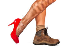Contrast between two shoes. Red high hill and walking boots stock images