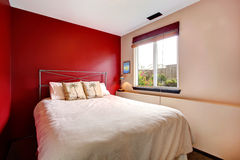 Contrast wall bedroom with tropical bedding. Small bedroom with red and cream wall. Iron frame bed with tropical theme bedding Royalty Free Stock Images