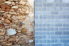 Contrast between wall styles. The wall of an old building meets the wall of a new one - the clash of styles conveys an interesting visual and conceptual contrast Royalty Free Stock Photos