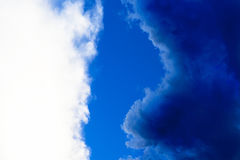 Contrast between white and dark blue clouds in a clear blue sky. Contrast between white and dark blue clouds, still rainy after a violent thunderstorm in a clear Stock Photography
