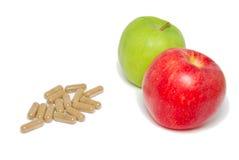 Contraste de manzanas y de cápsulas médicas Imagen de archivo