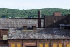 Contraste de montes verdes florestados atrás de deteriorar armazéns industriais fotografia de stock