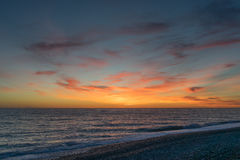 Contrasting sunset over dark blue sea. Cirrus colored clouds at sunset Royalty Free Stock Photo