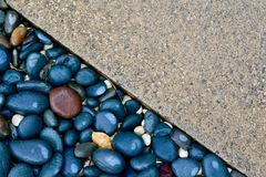Contrast textures of a paved driveway and pebbled sidewalk. Background image. Contrasting texture and colours of two different surfaces; interesting contrast royalty free stock photo