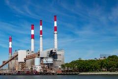 Contrasto delle torri del fumaiolo della centrale elettrica contro cielo blu Immagine Stock