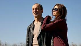 Contrasto nell'età Un uomo anziano e una giovane donna Una giovane moglie viene su dietro il suo marito e lo abbraccia stock footage