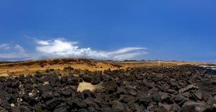 Contrasto nero della roccia con la sabbia arancio fotografie stock libere da diritti
