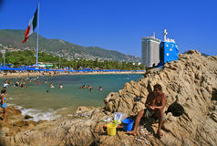 Contrasts: Hip and simple life in Acapulco, Mexico. Fisherman at Acapulco beach Stock Photography