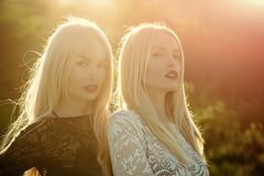 Contrasts and opposites concept. Two women with red lips and long blond hair. Beauty and fashion. Sisters twins posing on sunny natural landscape. Dualism and royalty free stock photo