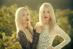 Contrasts and opposites concept. Dualism and dualistic nature. Beauty and fashion. Sisters twins posing on natural landscape. Two women with red lips and long royalty free stock photography
