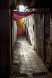 Contrastverkoop Marokko De smalle straat van de oude stad en de oude, afgebroken muren van huizen onder een rode luifel in de zom stock foto