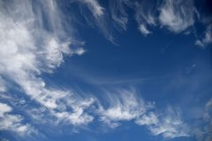 Contrasty Sky. A contrasty blue cloudy sky photographed during the day Stock Photo
