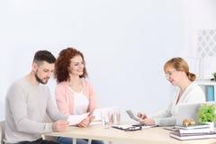 Contrat de signature de jeunes couples à l'agence d'assurance Photographie stock